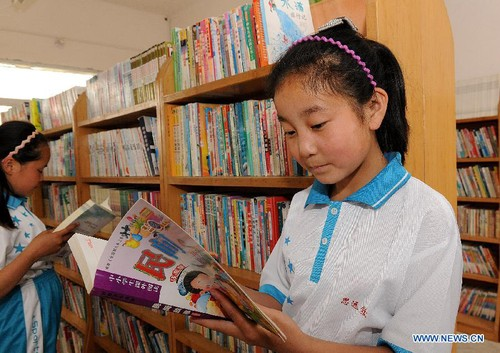 Bao Jingru, a young girl whose parents have left hometown to work in cities, reads books at a library in Siyuan School at Dashi Village of Guandao Township in Weinan City, northwest China's Shaanxi Province, May 22, 2012. A total of 320 children, accounting for 65.9 percent of the whole students, study and live in this boarding school while their parents work in faraway cities.
