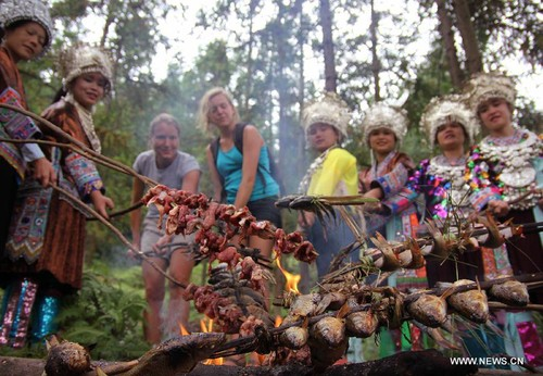 Tourists from France barbecue with women from Miao ethnic group in Gaowen Village of Miao Autonomous County of Rongshui, south China's Guangxi Zhuang Autonomous Region, Oct. 3, 2012. Tourists from home and abroad participated in a series of activities held by local people to celebrate China's National Day holiday. [Xinhua]
