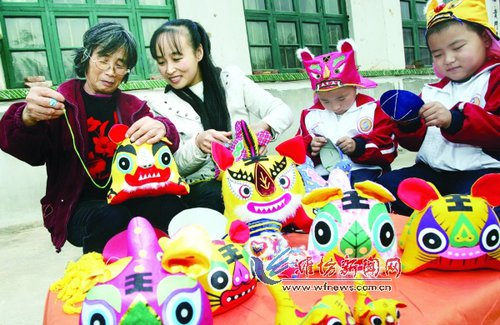 An elderly woman teaches her granddaughter how to make cloth tiger puppets. [wfnews.com.cn]